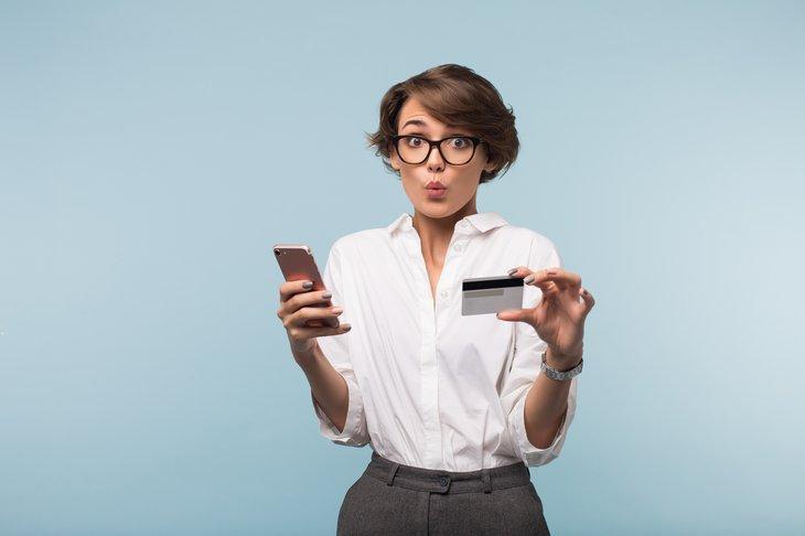 Une femme avec un smartphone et une carte de crédit est prise par surprise