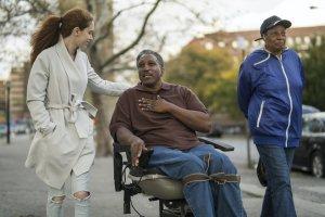 Une adolescente blanche parle avec un homme et une femme afro-américains handicapés lorsqu'ils marchent dans la rue du Bronx, à New York, ensemble